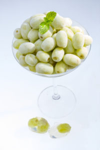 Frozen grape in martini glass.